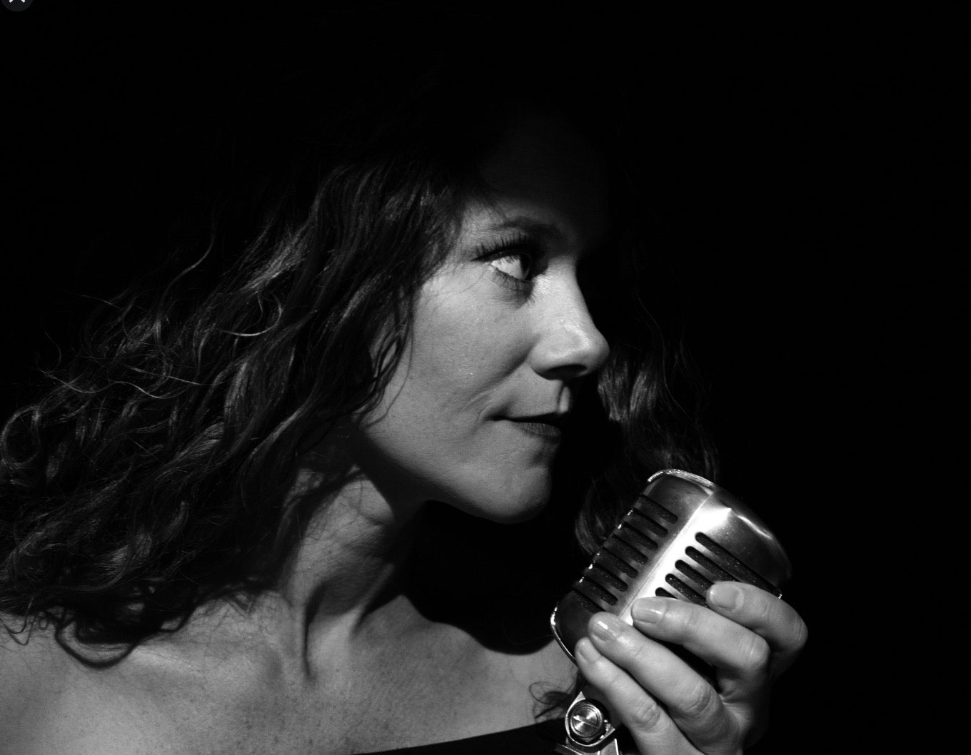 Woman with curly hair holding an old-style microphone and looking to the side
