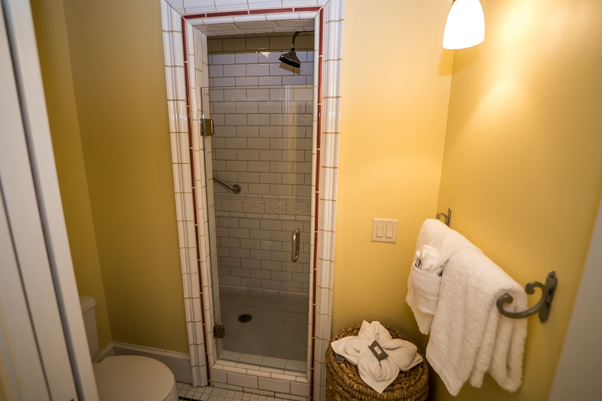 Walk-in shower, toilet, and white towels hanging on a rack