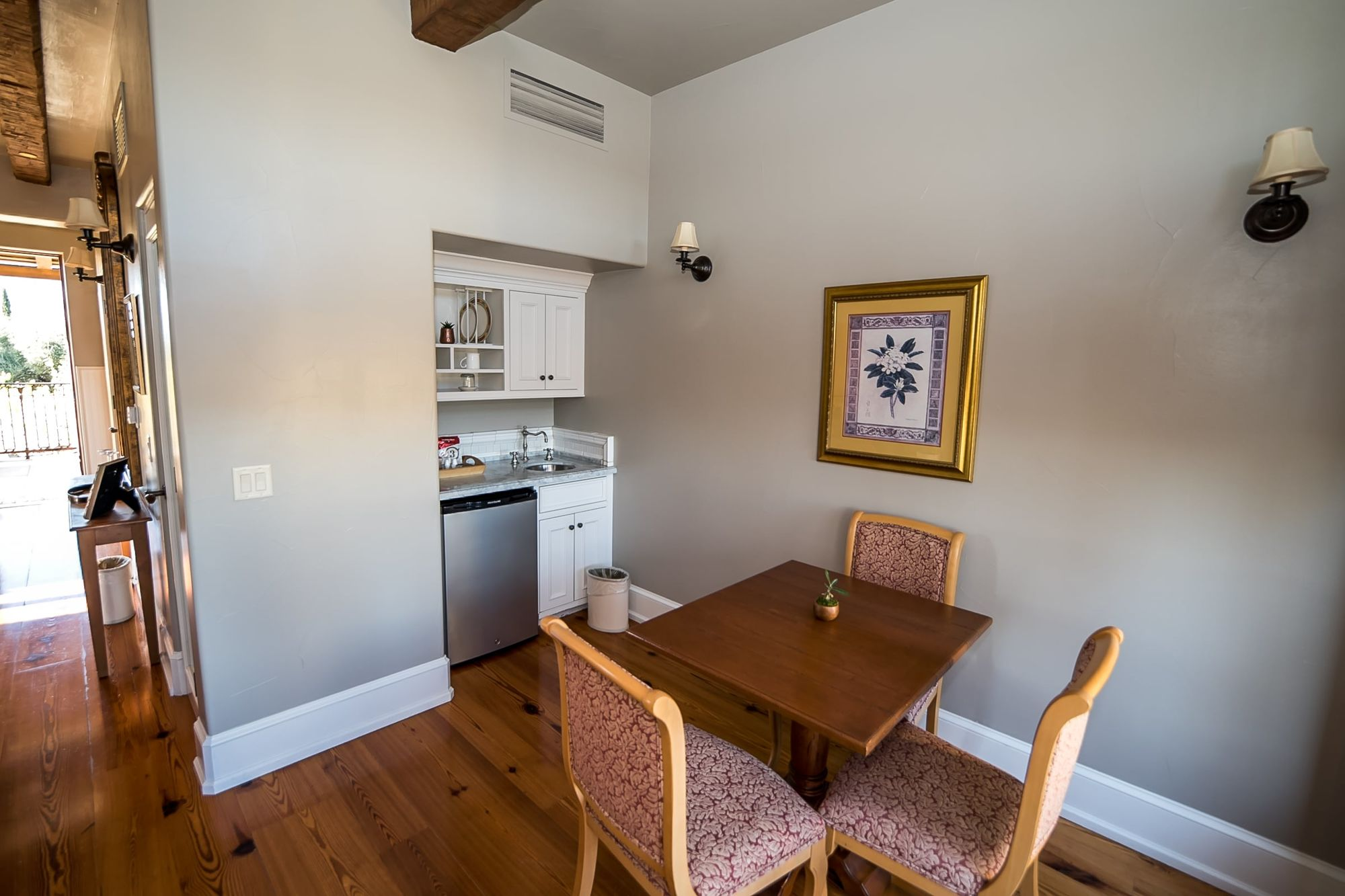 Small wet bar with sink fridge, table, and seating for three