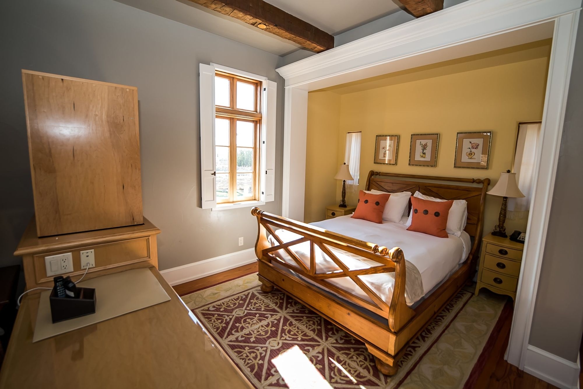 Bed room space with sleigh bed made up with white sheets and orange accent pillows