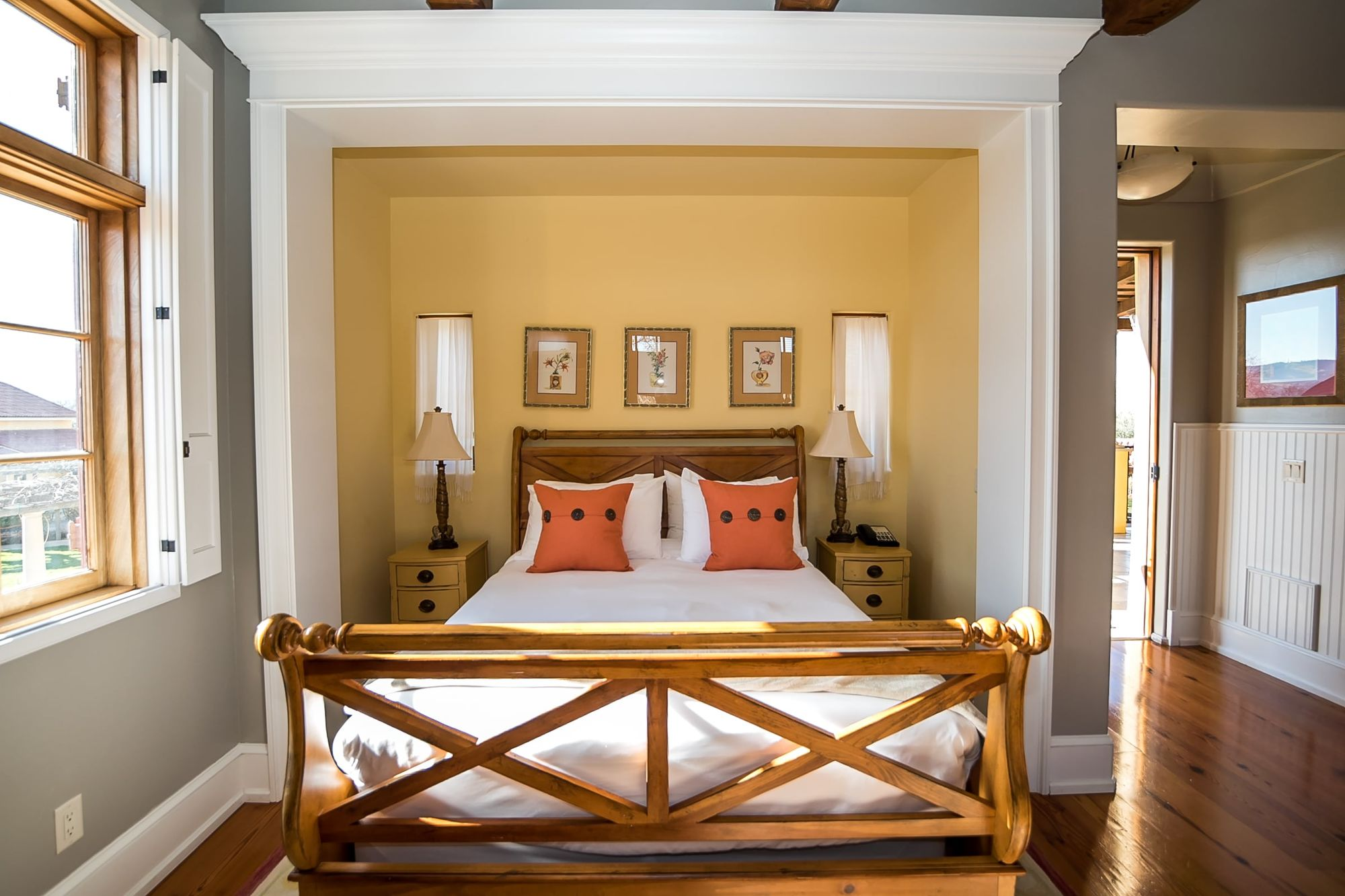 Sleigh bed made up with white sheets and orange accent pillows