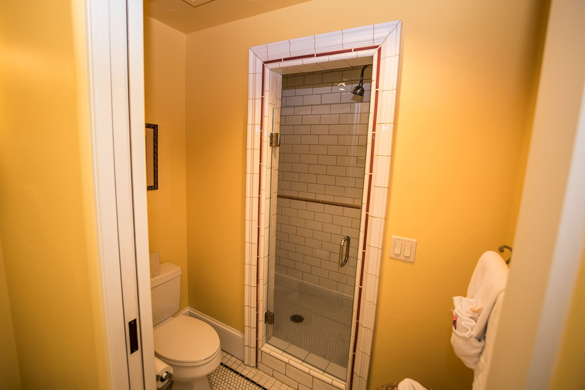 Door to walk-in shower with toilet and full rack of towels in the foreground