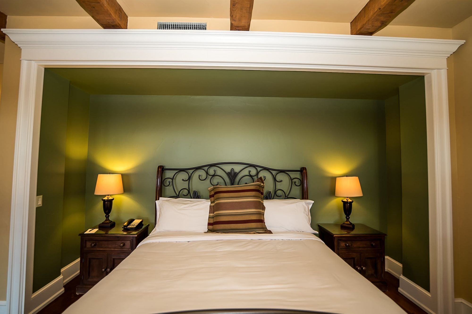 Bed with green walled niche and lights on each side