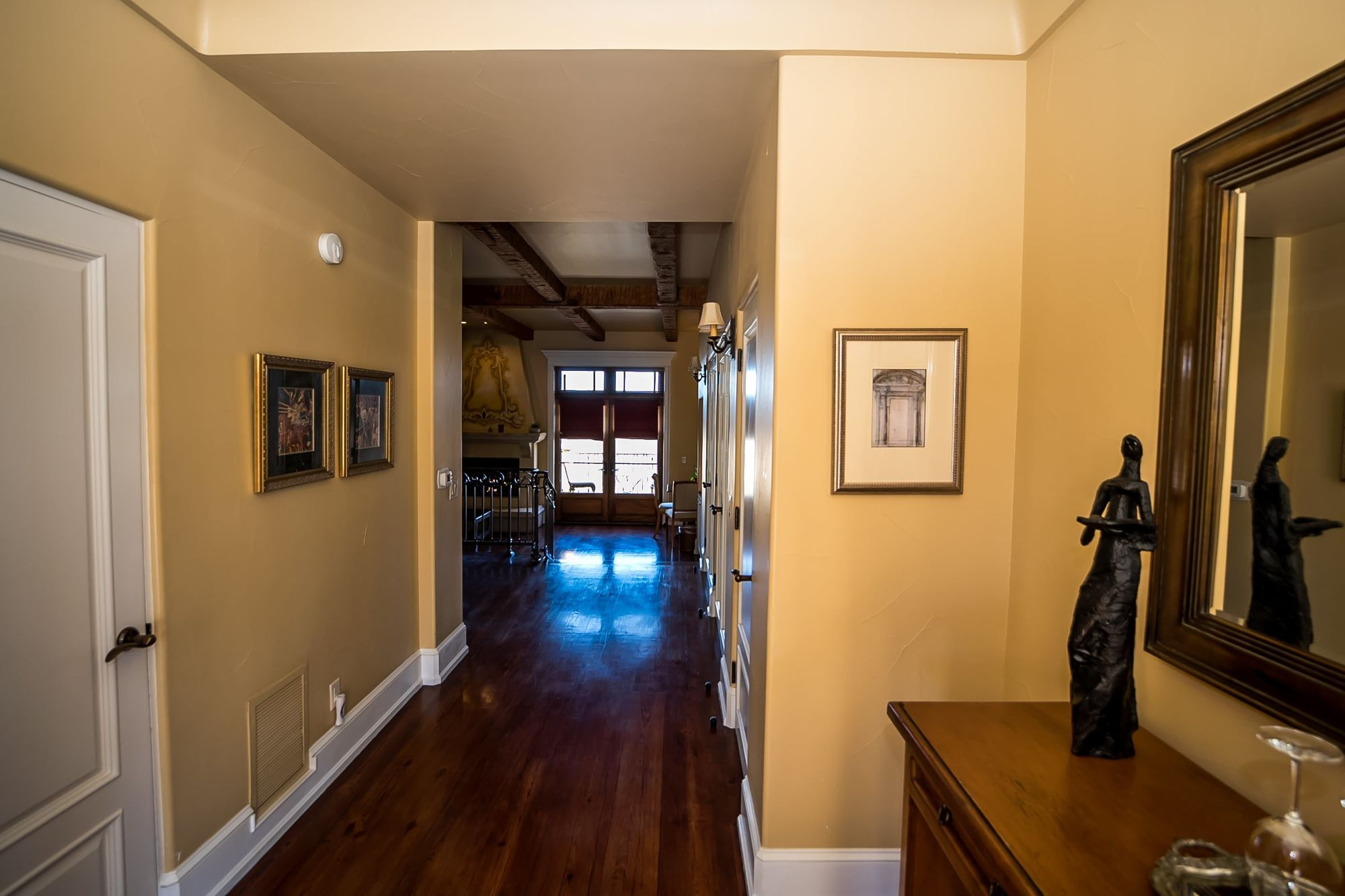 Hallway with side bar to the right and French doors at the end
