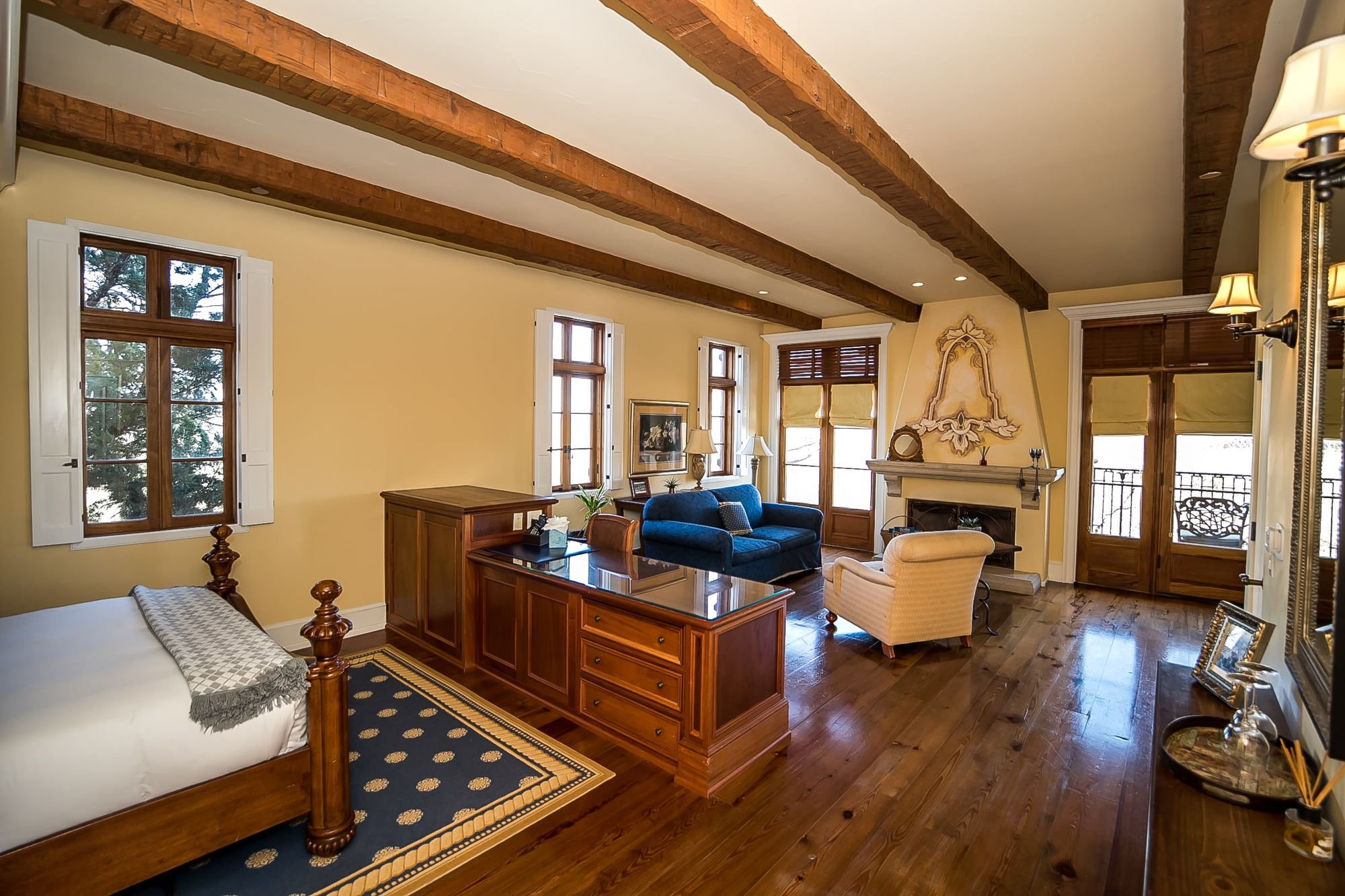 Room with rafters on the ceiling and a decorative fireplace with blue couch and chair in front