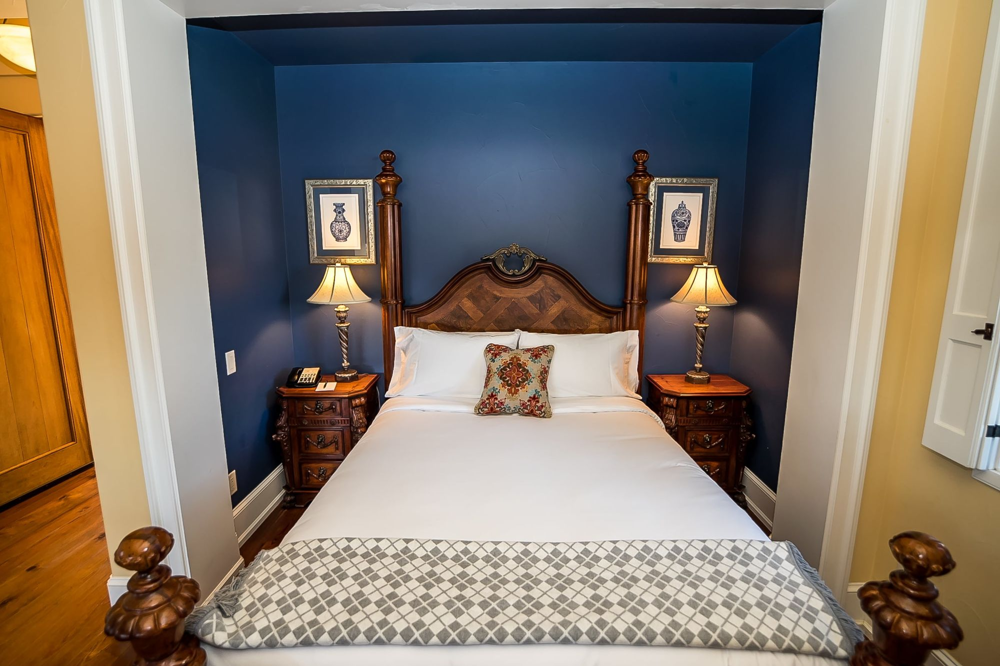 Bed made with white sheets with an accent pillow set in a niche painted dark blue