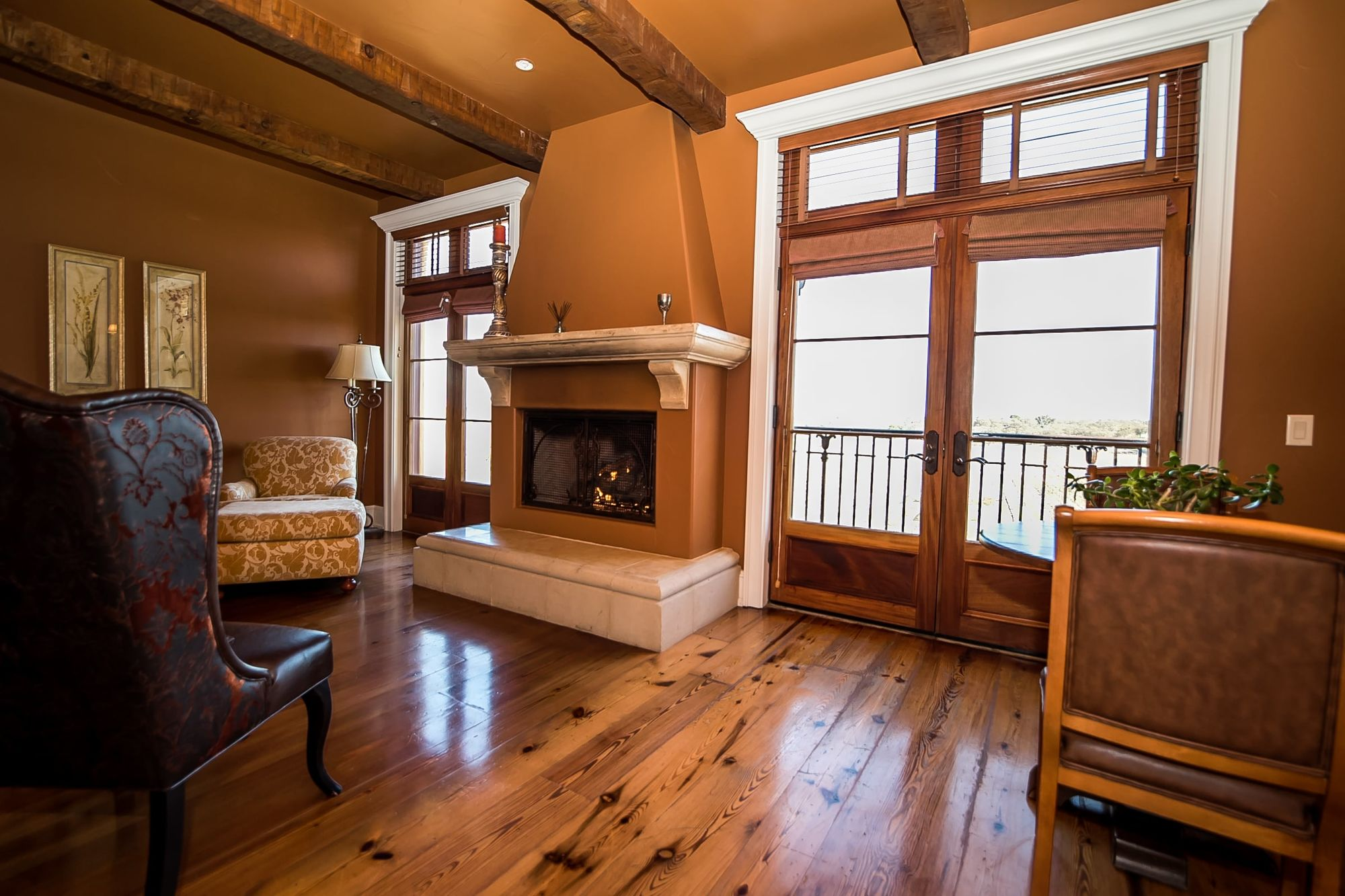 Sitting room with decorative fireplace and French doors