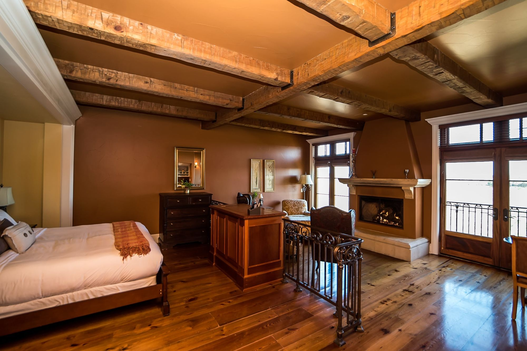 Combined bed room and sitting room with rafters on the ceiling