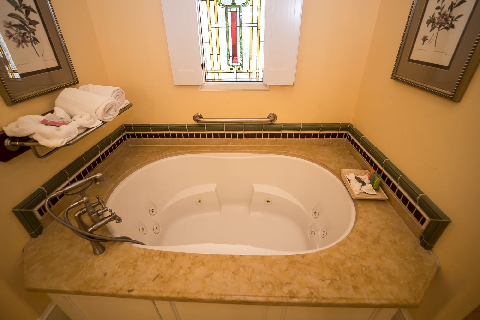 Spa bathtub with pile of towels to the left and soaps in a dish to the right