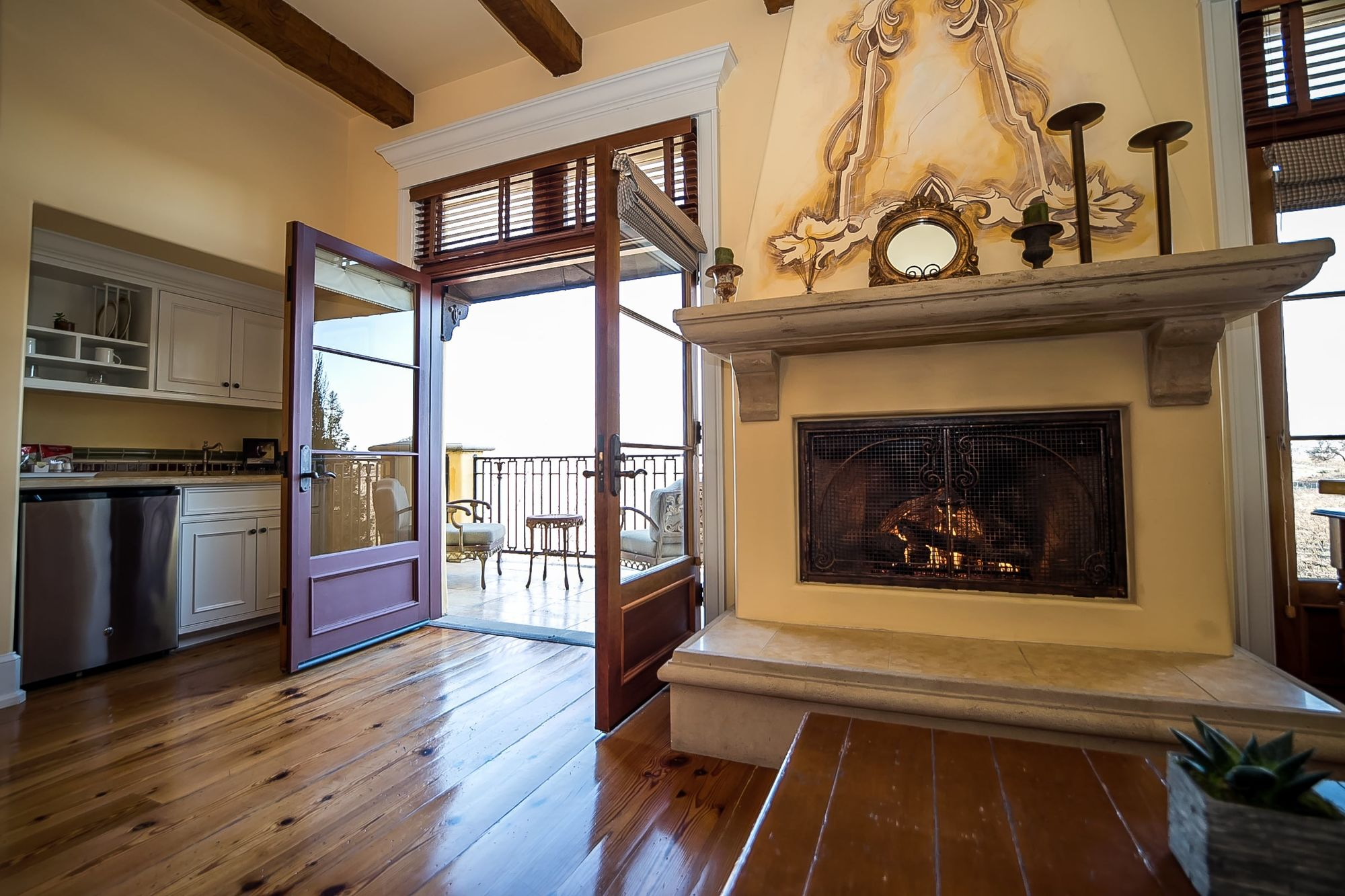 Decorative fireplace with French doors open to the patio to the left and the wet bar behind the door