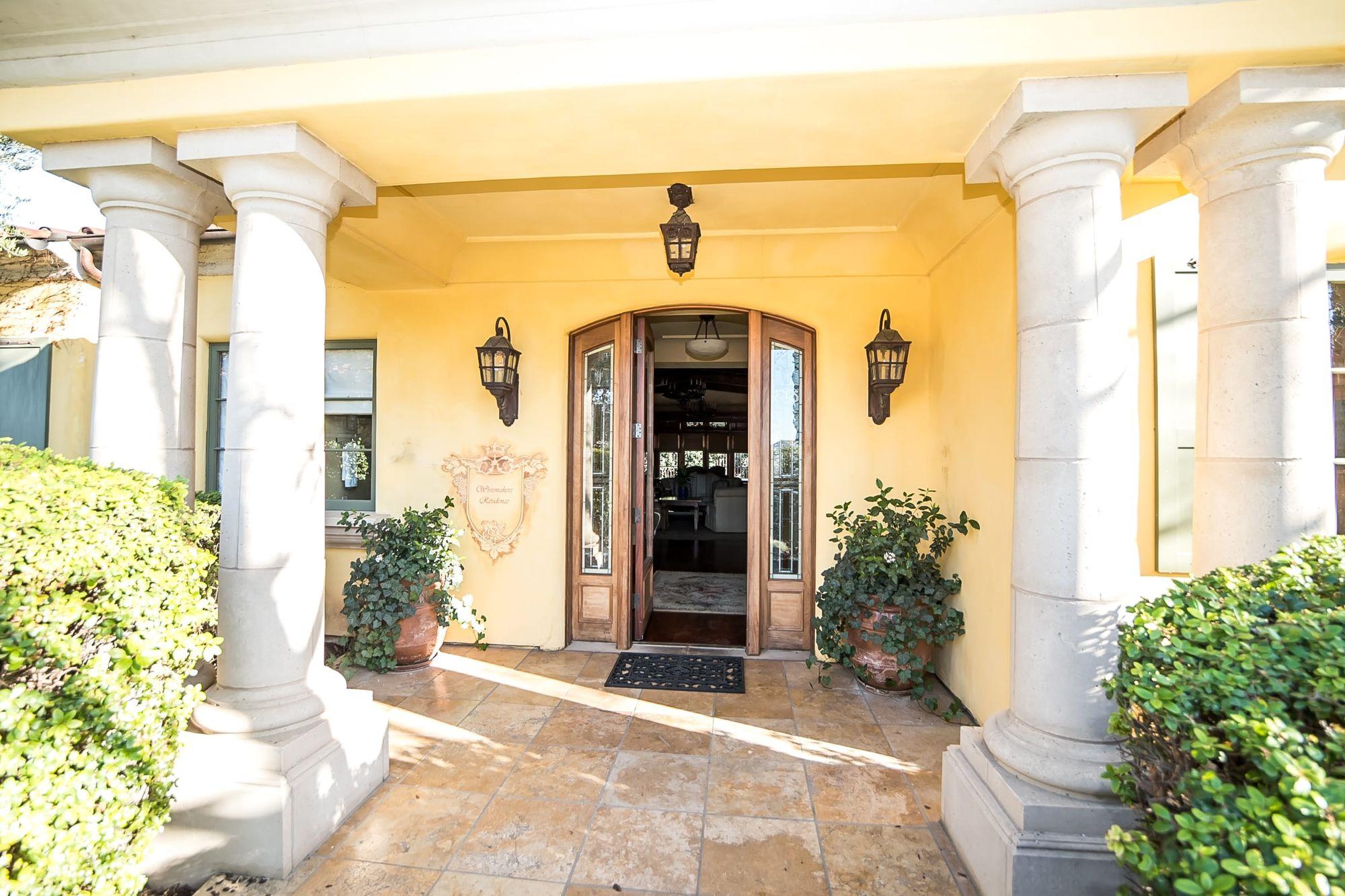 Front door open with lighting and columns