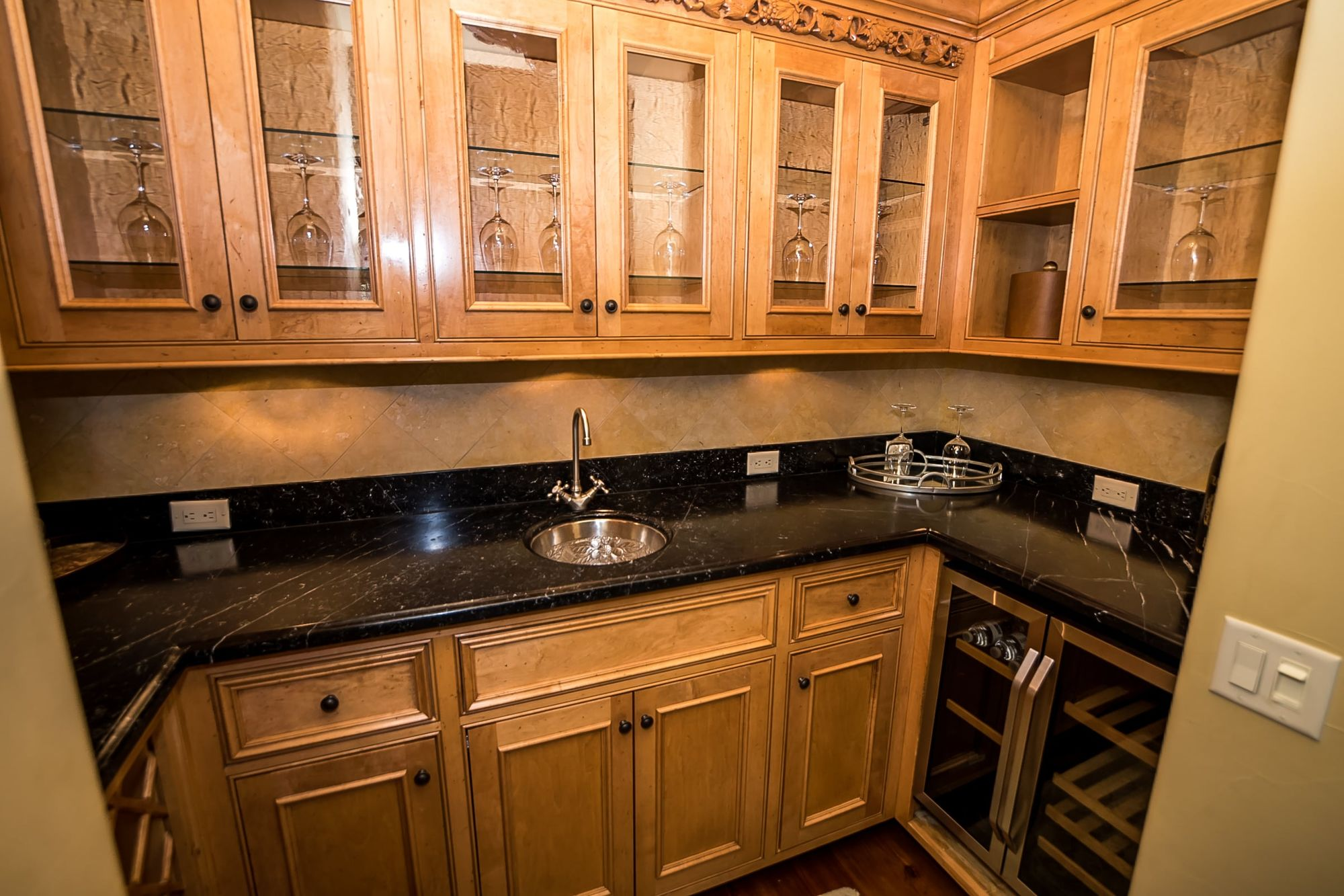 Large wet bar with sink, wine fridge, and glasses in cabinets above
