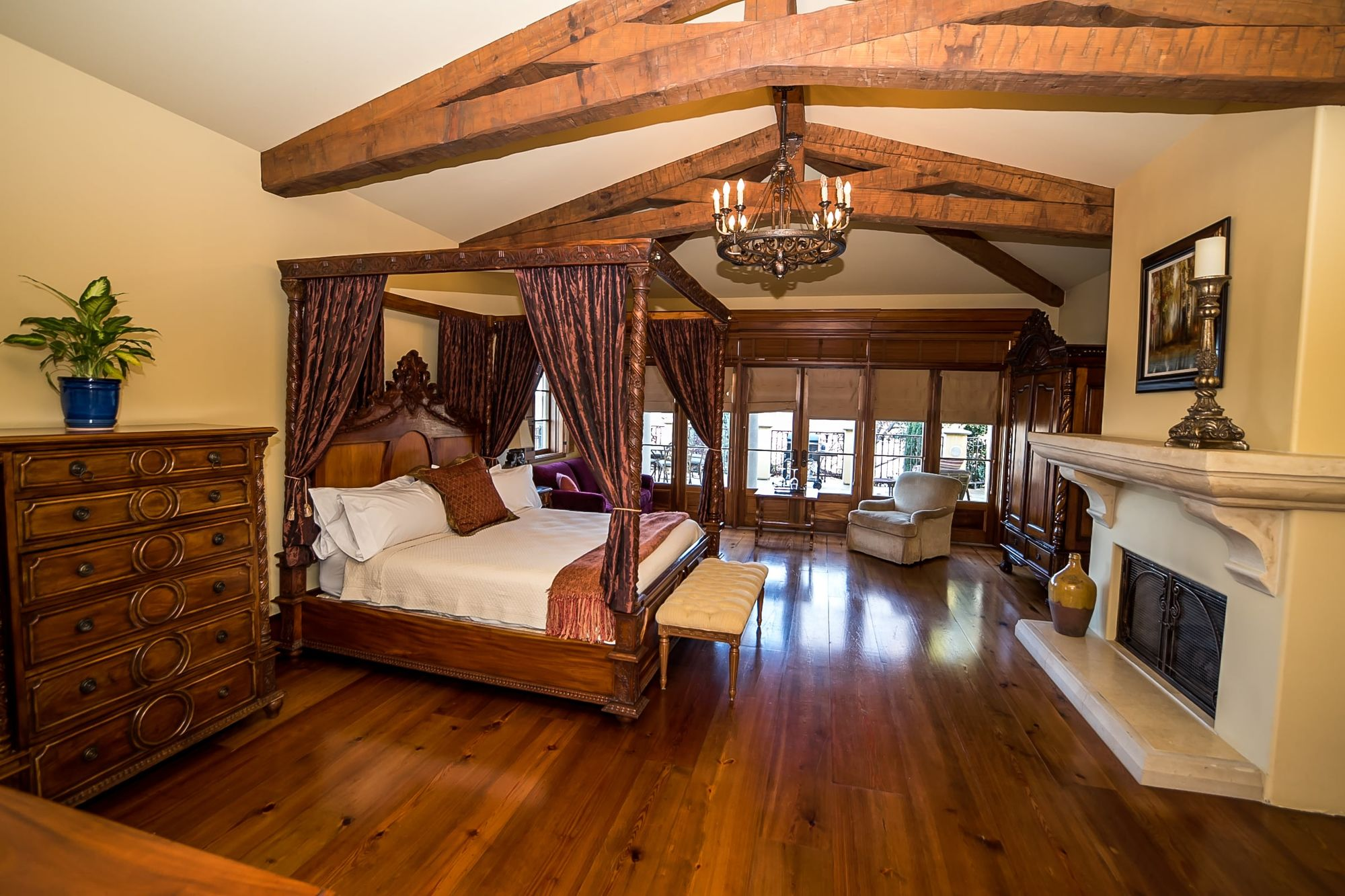 Big wooden rafters with canopy bed to the left and chest of drawers and decorative fireplace to the left