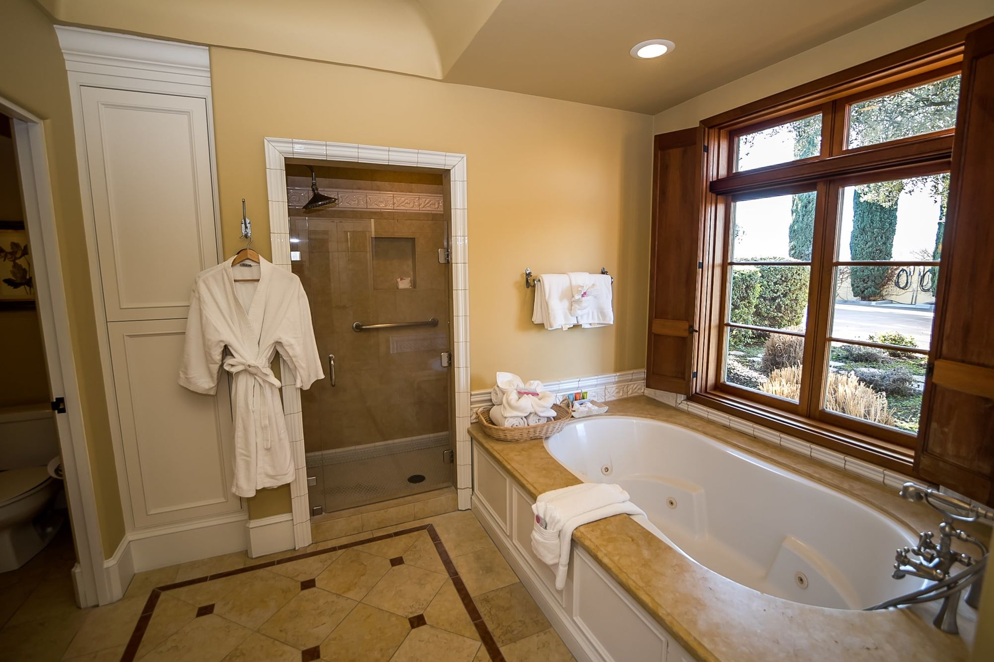 Spa bathtub with walk in shower to the side and a robe hanging on a hook