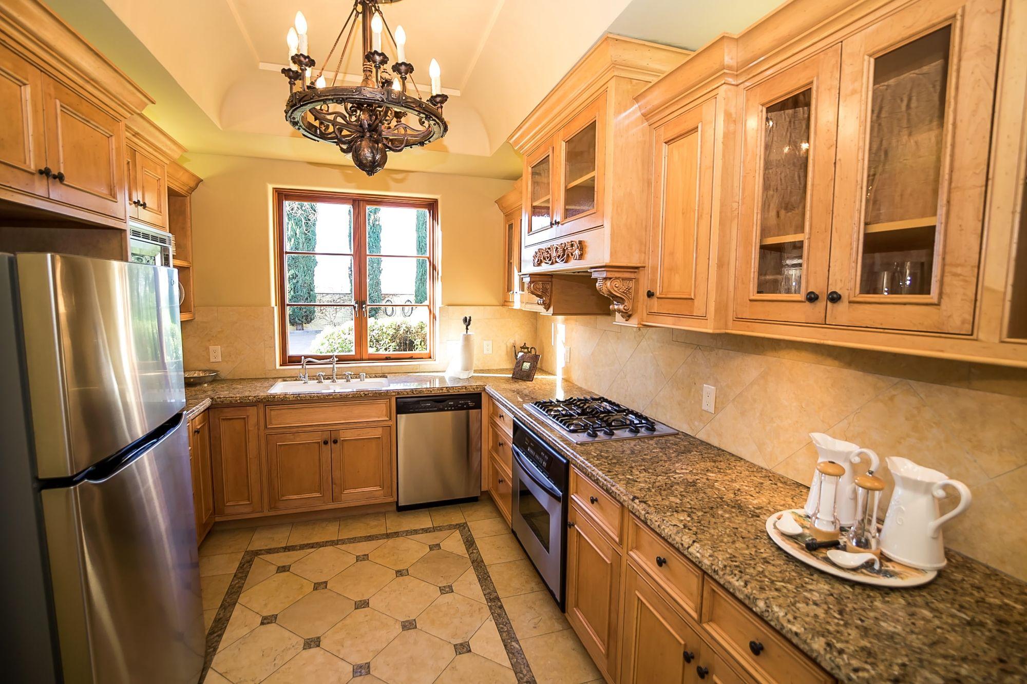 Kitchen with a chandelier, granite countertops, fridge, gas range, and sink under the window