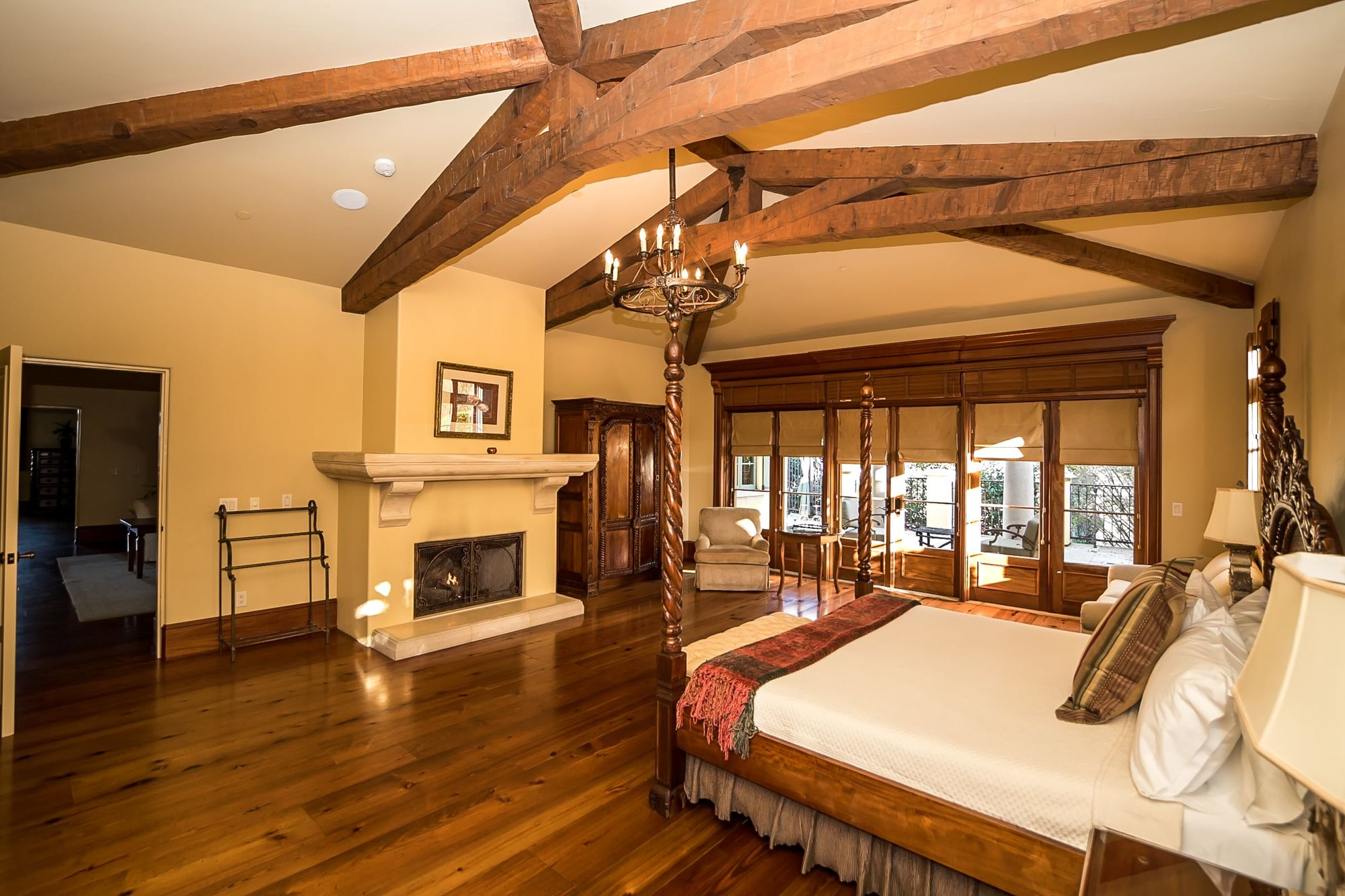 Bedroom with rafter ceilings with French doors and a four post bed