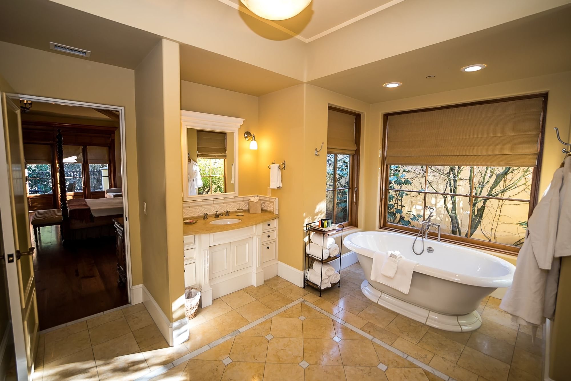 Bathroom with vanity, small shelf stacked with rolled towels and a garden tub