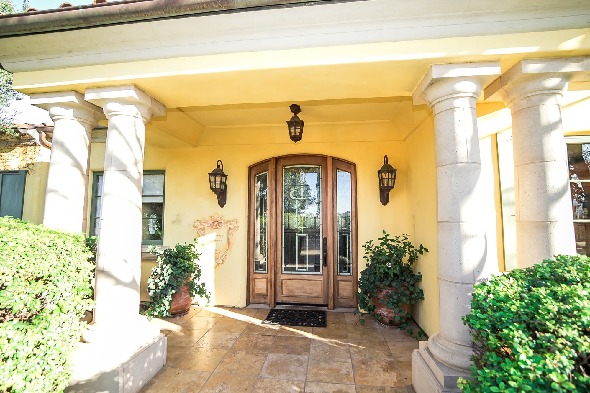 Front door with lighting and columns on either side