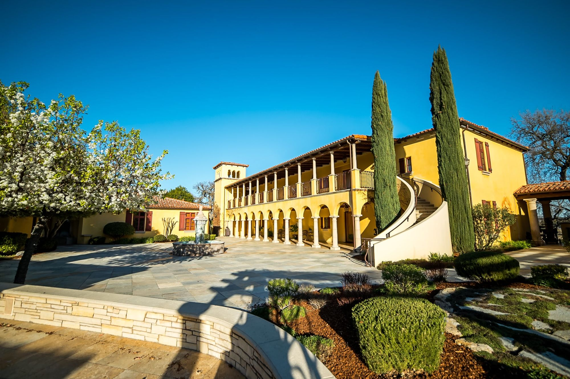 Italian style building with flag stone patio and cypress trees