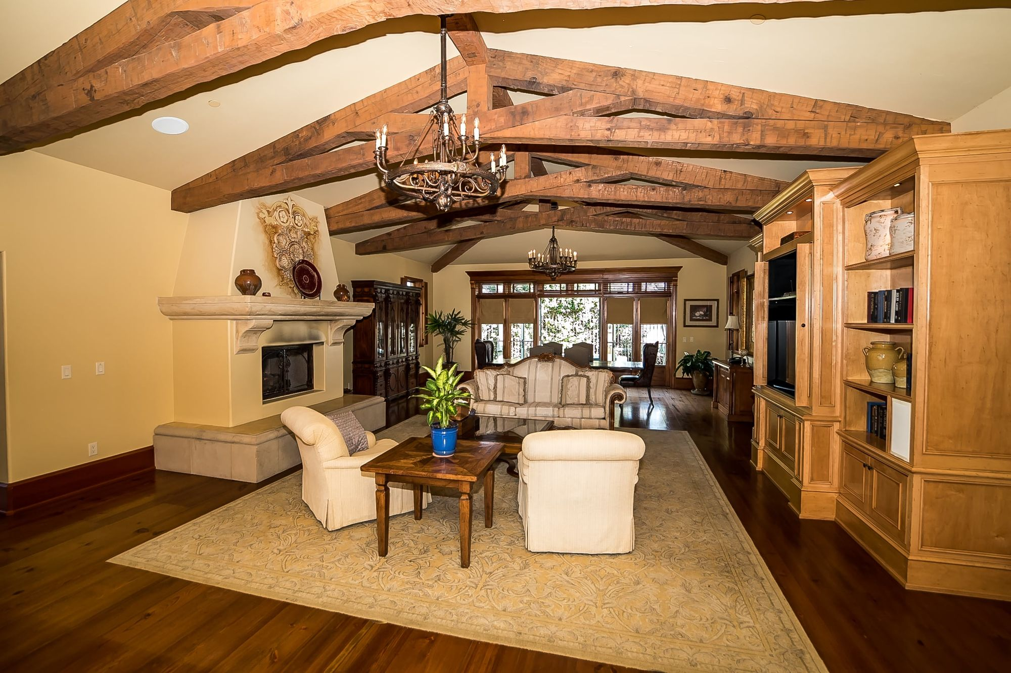 Sitting room with decorative fireplace, television cabinet, chandeliers suspended from the ceiling with rafters