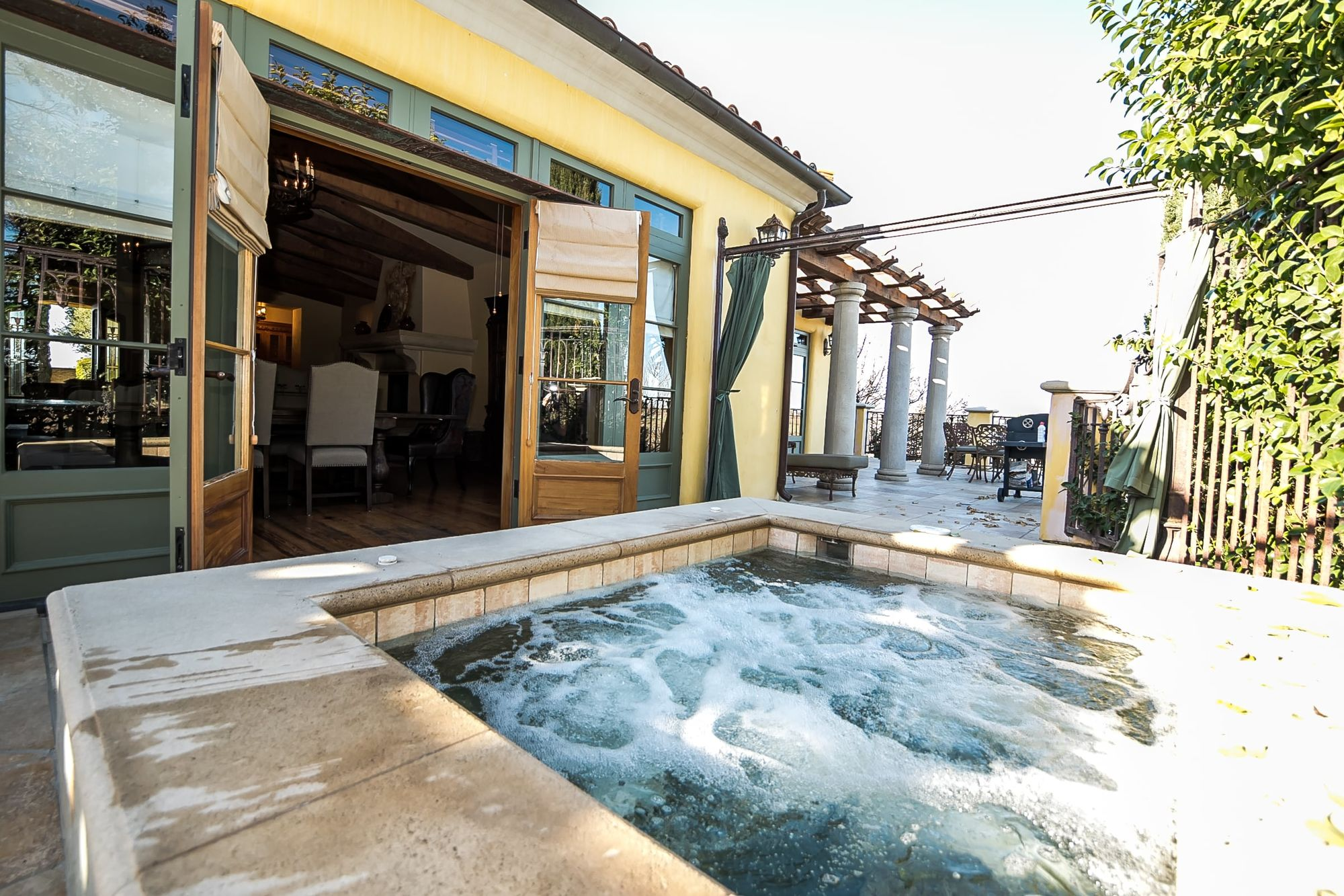 Hot tub bubbling on patio outside open French doors